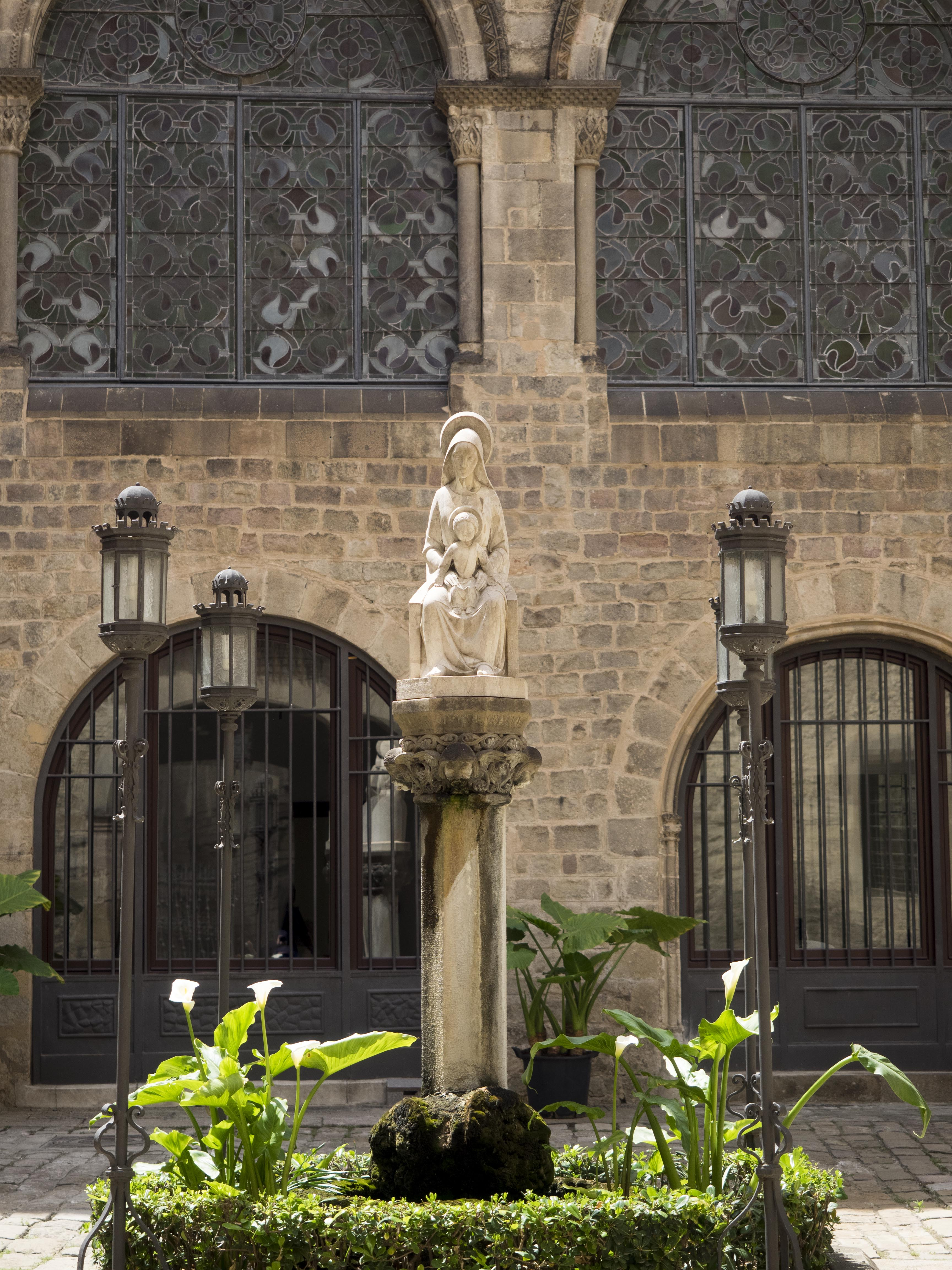 A saint on a plinth in a government building courtyard